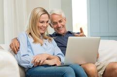 Couples travaillant sur l'ordinateur portatif Photographie stock libre de droits