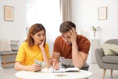 Couples tristes comptant l'argent dans la vie images stock