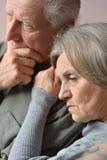 Couples tristes d'aîné sur le fond brun Photo stock