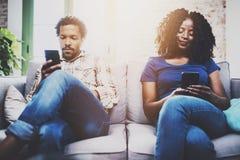Couples tristes d'afro-américain détendant ensemble sur le sofa Jeune homme de couleur et son amie à l'aide des périphériques mob Images libres de droits