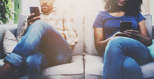 Couples tristes d'afro-américain détendant ensemble sur le sofa Jeune homme de couleur et son amie à l'aide des périphériques mob Photos libres de droits
