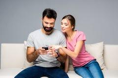 Couples utilisant des smartphones Images stock
