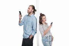 Couples utilisant des smartphones tout en se tenant séparé par le mur Images stock