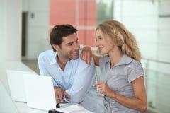 Couples utilisant deux ordinateurs portatifs Photographie stock libre de droits
