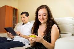 Couples utilisant l'Internet à lire les réseaux sociaux Photo stock