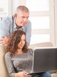 Couples utilisant l'ordinateur portable à la maison photos libres de droits