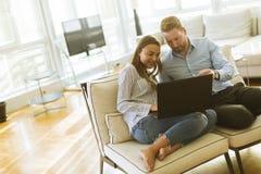 Couples utilisant l'ordinateur portable dans la chambre photos libres de droits