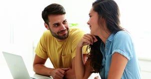 Couples utilisant l'ordinateur portable dans la cuisine clips vidéos