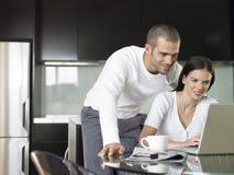Couples utilisant l'ordinateur portable dans la cuisine moderne Photo libre de droits