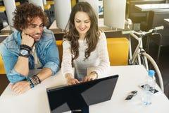 Couples utilisant l'ordinateur portable dans le restaurant Photos stock