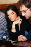 Couples utilisant l'ordinateur portable en café Photographie stock libre de droits