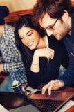 Couples utilisant l'ordinateur portable en café Images stock