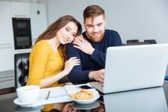 Couples utilisant l'ordinateur portable à la maison Photos stock