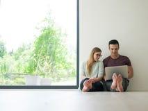Couples utilisant l'ordinateur portable sur le plancher à la maison Images stock