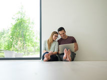 Couples utilisant l'ordinateur portable sur le plancher à la maison Photographie stock