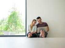 Couples utilisant l'ordinateur portable sur le plancher à la maison Image libre de droits