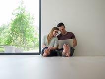 Couples utilisant l'ordinateur portable sur le plancher à la maison Photographie stock libre de droits
