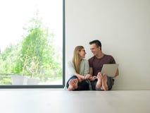 Couples utilisant l'ordinateur portable sur le plancher à la maison Photo stock