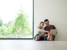 Couples utilisant l'ordinateur portable sur le plancher à la maison Photos libres de droits