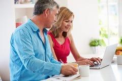 Couples utilisant l'ordinateur portable tandis que prenant le petit déjeuner dans la cuisine Photo libre de droits