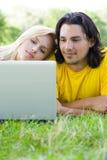 Couples utilisant l'ordinateur portatif à l'extérieur Photographie stock