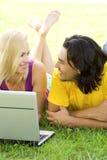 Couples utilisant l'ordinateur portatif à l'extérieur Images libres de droits