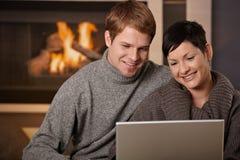 Couples utilisant l'ordinateur portatif à l'hiver Image stock