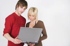 Couples utilisant l'ordinateur portatif Photographie stock