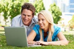 Couples utilisant l'ordinateur portatif en stationnement de ville Image libre de droits