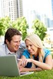 Couples utilisant l'ordinateur portatif en stationnement de ville Image stock