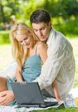 Couples utilisant l'ordinateur portatif ensemble Images stock