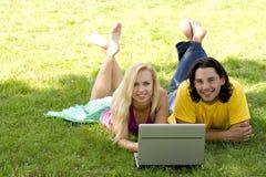 Couples utilisant l'ordinateur portatif à l'extérieur Image stock