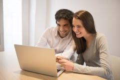 Couples utilisant la carte de crédit à faire des emplettes sur la ligne Ordinateur portatif Bureau d'intérieur Image stock