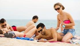 Couples utilisant la crème pour le coup de soleil Images libres de droits