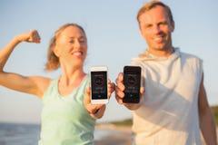 Couples utilisant la forme physique APP à leurs téléphones portables image stock