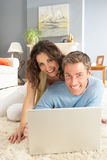 Couples utilisant la pose de détente d'ordinateur portatif sur la couverture à la maison Images stock