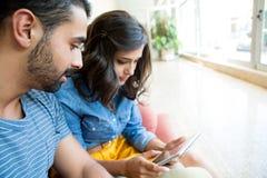 Couples utilisant la tablette Photographie stock libre de droits