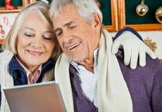 Couples utilisant la Tablette de Digital au magasin de Noël Photographie stock