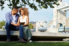 Couples utilisant la Tablette de Digital avec le pont de tour à l'arrière-plan Image libre de droits
