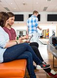 Couples utilisant la Tablette de Digital dans le club de bowling Image libre de droits
