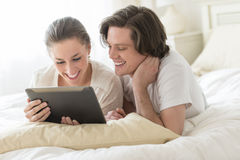 Couples utilisant la Tablette de Digital dans le lit Photographie stock libre de droits