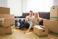 Couples utilisant le comprimé en leur nouvel appartement image stock