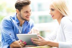 Couples utilisant le comprimé numérique au café Photos stock