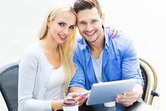 Couples utilisant le comprimé numérique au café Image libre de droits