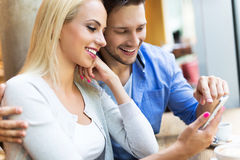 Couples utilisant le comprimé numérique au café Photographie stock