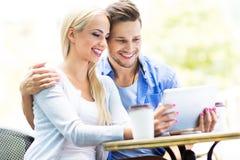 Couples utilisant le comprimé numérique au café Photos libres de droits
