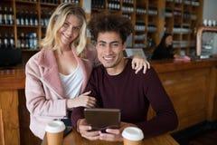 Couples utilisant le comprimé numérique dans la barre Photo stock
