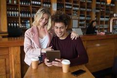 Couples utilisant le comprimé numérique dans la barre Images stock