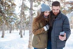 Couples utilisant le smartphone en parc d'hiver Photographie stock libre de droits