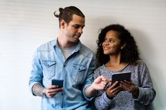 Couples utilisant le smartphone et le comprimé numérique photos stock